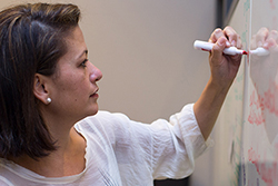 Woman writing on white board