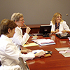 three nursing and healthcare educators sitting at a table