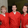 Three students in red scrubs